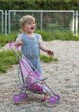 Kind met een stuk speelgoed kinderwagen stock afbeelding
