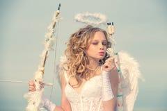 Kind met engelachtig karakter Gelukkig tienerengelenmeisje De mooie meisjescupido met boog en pijl is klaar om uw liefde te vinde stock foto's