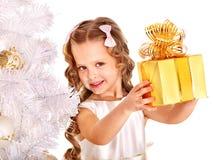 Kind met giftdoos dichtbij witte Kerstboom. Stock Foto