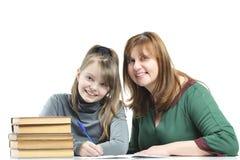 Kind met haar moeder die schoollessen doen Stock Fotografie