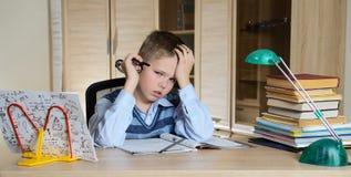 Kind met het leren van moeilijkheden Vermoeide jongen die thuiswerk doen Onderwijs Stock Foto