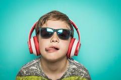 Kind met hoofdtelefoons van muziek en grappige uitdrukking stock fotografie