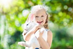 Kind met konijn Oostelijk Konijntje Jonge geitjes en huisdieren stock foto's