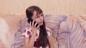 Kind met mobiel Meisje in een mooie kleding met een mobiele telefoon Meisje in een kleding met harten stock videobeelden