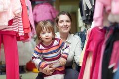 Kind met moeder bij klerenwinkel Royalty-vrije Stock Foto's