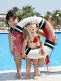 Kind met moeder dichtbij zwembad. stock fotografie