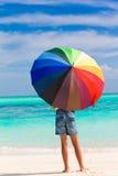 Kind met parasol op strand Stock Afbeeldingen