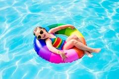 Kind met stuk speelgoed ring in zwembad stock foto's
