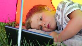 Kind met tablet die op groen gras onder zonparaplu liggen De vakantieconcept van de zomer stock footage