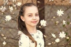 Kind met tot bloei komende bloemen openlucht Meisje op bloemenbloesem in de lente Schoonheidsjong geitje met verse blik en lang h royalty-vrije stock fotografie
