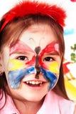 Kind met verf van gezicht in spelruimte. stock afbeelding