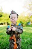 Kind in militaire eenvormig tegen aardachtergrond Stock Afbeeldingen