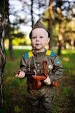Kind in militaire eenvormig tegen aardachtergrond Stock Foto