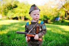 Kind in militaire eenvormig tegen aardachtergrond Royalty-vrije Stock Foto's