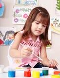 Kind mit Abbildung und Pinsel im Spielraum. Lizenzfreie Stockfotografie