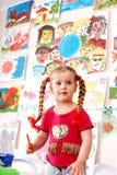 Kind mit Abbildung und Pinsel im Spielraum. Lizenzfreie Stockfotos