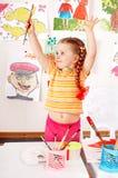 Kind mit Abbildung und Pinsel im Spielraum. Lizenzfreies Stockfoto