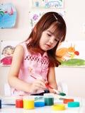 Kind mit Abbildung und Pinsel im Spielraum. Stockfoto