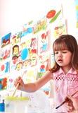 Kind mit Abbildung und Pinsel im Spielraum. Lizenzfreie Stockbilder
