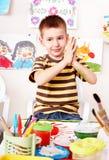 Kind mit Abbildung und Pinsel im Spielraum. Stockfotografie