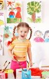 Kind mit Abbildung und Pinsel im Spielzimmer. Stockfotos