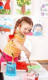Kind mit Abbildung und Pinsel im Spielzimmer. Lizenzfreies Stockbild