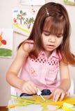 Kind mit Abbildung und Pinsel im Spielzimmer. Stockfotografie
