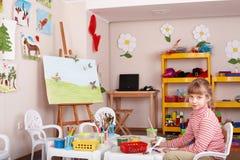 Kind mit Abbildung und Pinsel im Spielzimmer. Lizenzfreie Stockfotografie