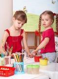 Kind mit Abbildung und Pinsel im Spielzimmer. Stockbild