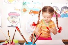 Kind mit Abbildung und Pinsel im Spielzimmer. Lizenzfreie Stockfotos