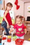 Kind mit Abbildung- und Pinselanstrich im Spielzimmer. Stockfotografie