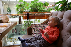 Kind mit Apfel auf Sofa Lizenzfreie Stockfotografie
