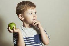 Kind mit Apfel Kleiner hübscher Junge mit grünem Apfel Biokost Corn Flakes Früchte Stockbild