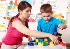 Kind mit Aufbau im Spielraum. Stockfotos