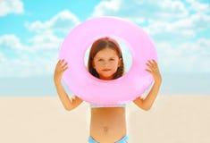 Kind mit aufblasbarem Kreis auf dem Strand Stockfoto