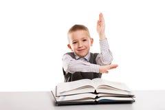 Kind mit Büchern am Schreibtisch Hand für antwortende Schule oben gestikulierend Lizenzfreies Stockfoto