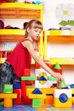 Kind mit Block im Spielraum. Lizenzfreie Stockbilder