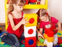 Kind mit Block und Aufbau im Spielraum. Stockfotografie