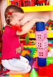 Kind mit Block und Aufbau im Spielraum. Stockbild