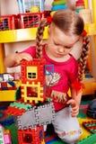 Kind mit Block und Aufbau stellte in Spielzimmer ein. Lizenzfreie Stockfotos