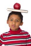 Kind mit Buch und Apple über seinem Kopf Stockfotografie
