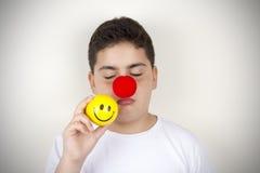 Kind mit Clown Nose und Lächeln-Gesichts-Spielzeug Lizenzfreie Stockfotografie