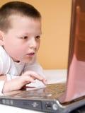 Kind mit Computer Stockfotografie