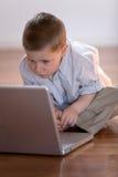 Kind mit Computer zu Hause Lizenzfreie Stockbilder