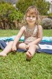 Kind mit dem Badeanzug, der auf Tuch auf grünem Gras sitzt Lizenzfreies Stockbild