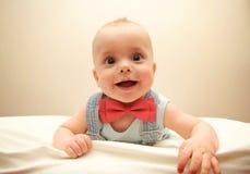 Kind mit dem bowtie, das auf dem Bett liegt Stockfoto