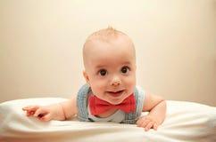 Kind mit dem bowtie, das auf dem Bett liegt Lizenzfreie Stockfotos