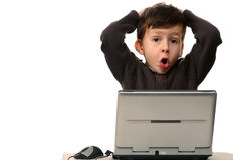 Kind mit dem entsetzten Gesicht, das vor Laptop sitzt Lizenzfreie Stockbilder
