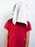Kind mit dem Kopf versteckt vom Staubtuch Stockbild