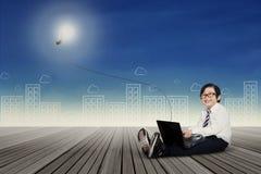 Kind mit dem Laptop, der an Glühlampe anschließt Stockbilder